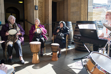Three elderly ladies are seated playing percussion instruments and singing