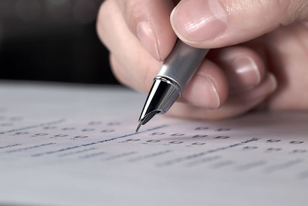 Pen in hand hovering over paper report