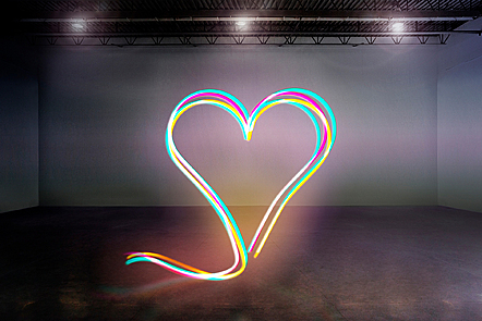 Computer generated image of a heart shape made out of coloured neon tubes.