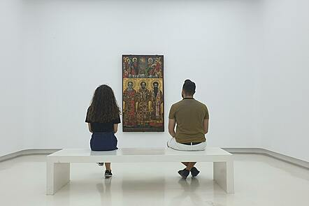 Two people sitting on a white bench looking at a medieval painting in a gallery setting.