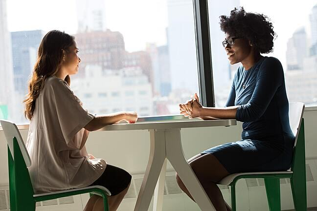 Two women sitting at a desk near a window and chatting