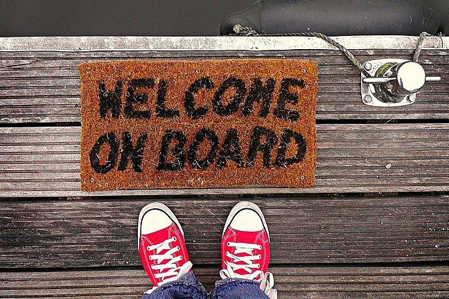 A doormat which says 'Welcome on Board'. Twp feet standing beside it.