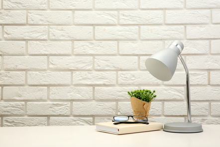 An image of a white desk with books and a lamp