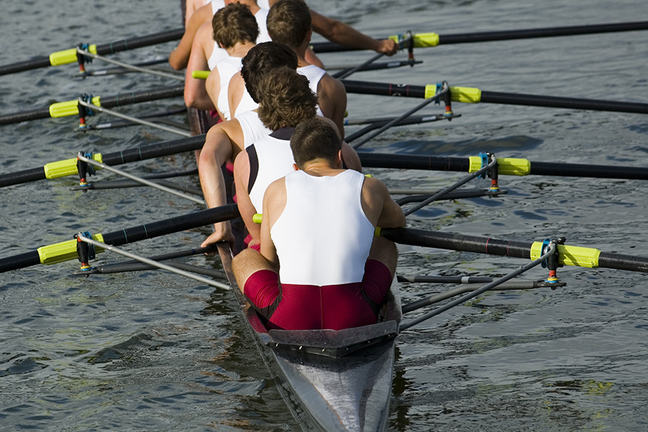 A rowing team in a racing scull on the water.