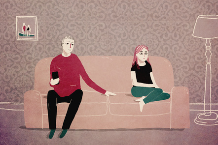 A couple sits at either end of a sofa: they are together, but seem to be in their own separate worlds.