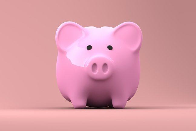 A photo of a small pink ceramic piggy bank on a table.