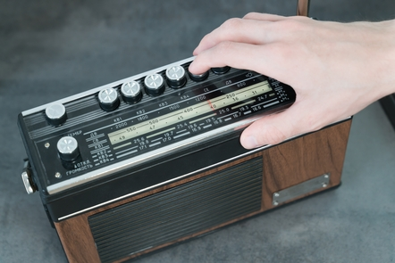 A hand is tuning in a button on an old style portable radio