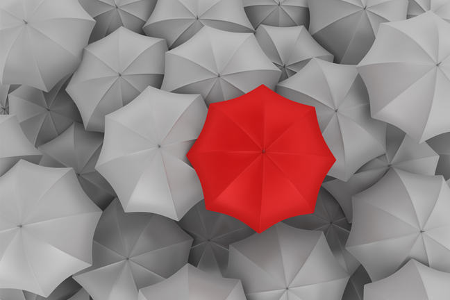 Red umbrella in group of grey umbrellas