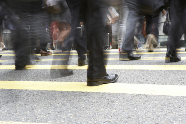 Lower legs with black shoes and trousers walking across a yellow pedestrian crossing.
