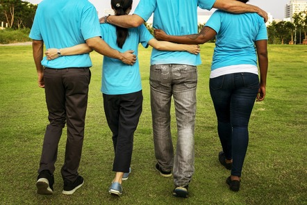 the back of four people walking with arms around each other