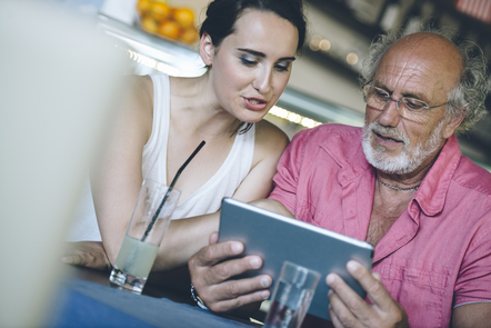 A young woman and a mature man sitting together looking at a tablet smart device.