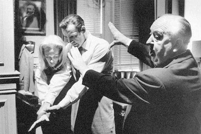 Image of Hitchcock directing the film two actors on the set of *Marnie*