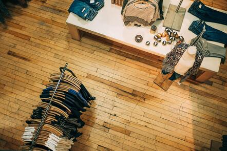 An aerial shot of a clothing store floor. There is a rack of clothes and a table with accessories.