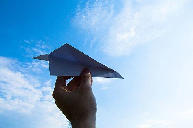 Paper plane being held up in the air