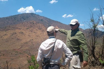 Geologists in the field looking at a hilly landscape