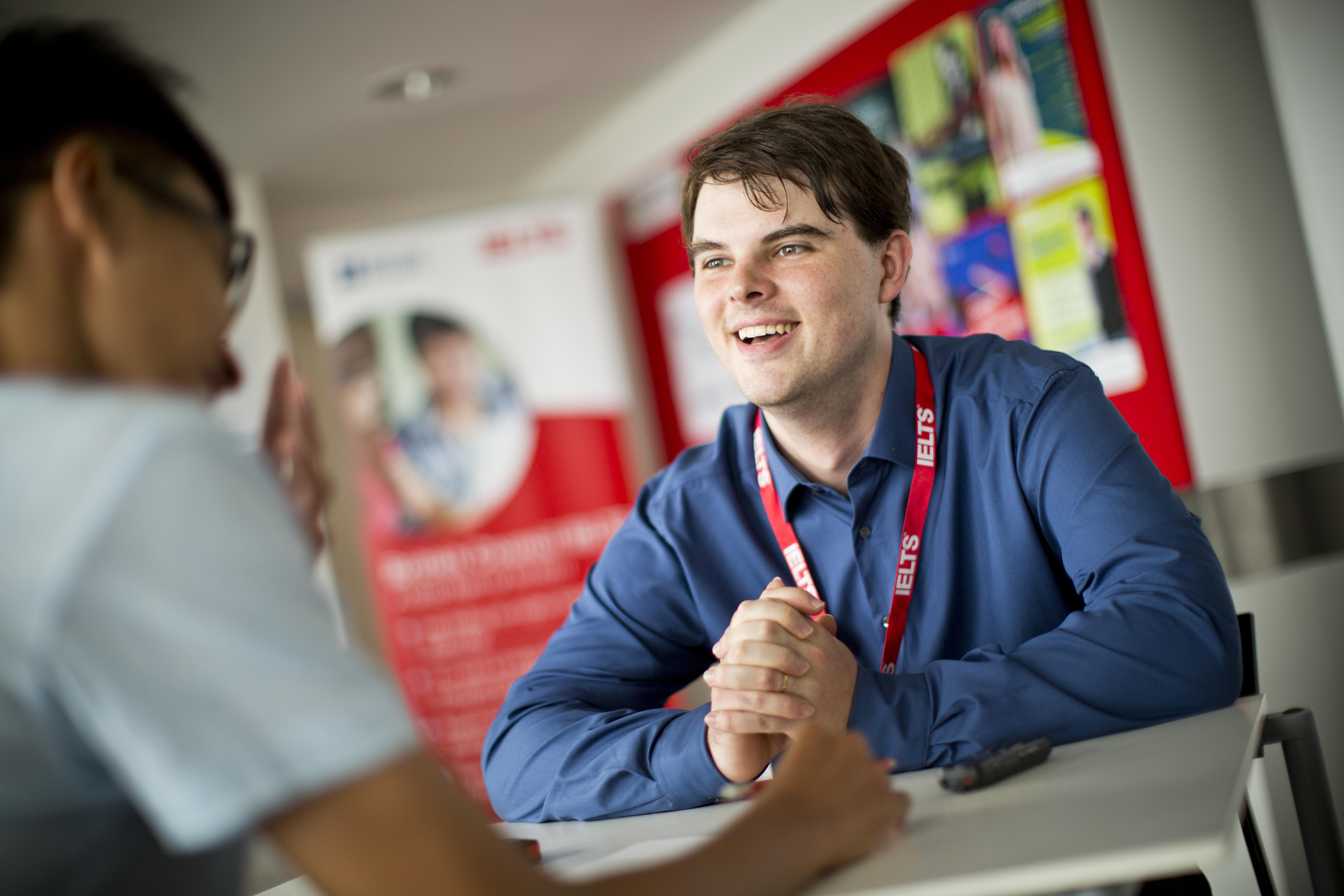 A smiling interviewer talks to an IELTS candidate