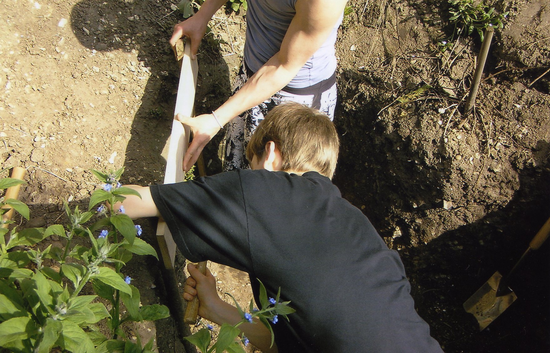 A photo of 2 pupils outside digging a hole in the ground
