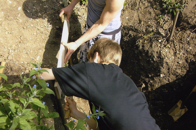A photo of 2 students outside digging a hole in the ground