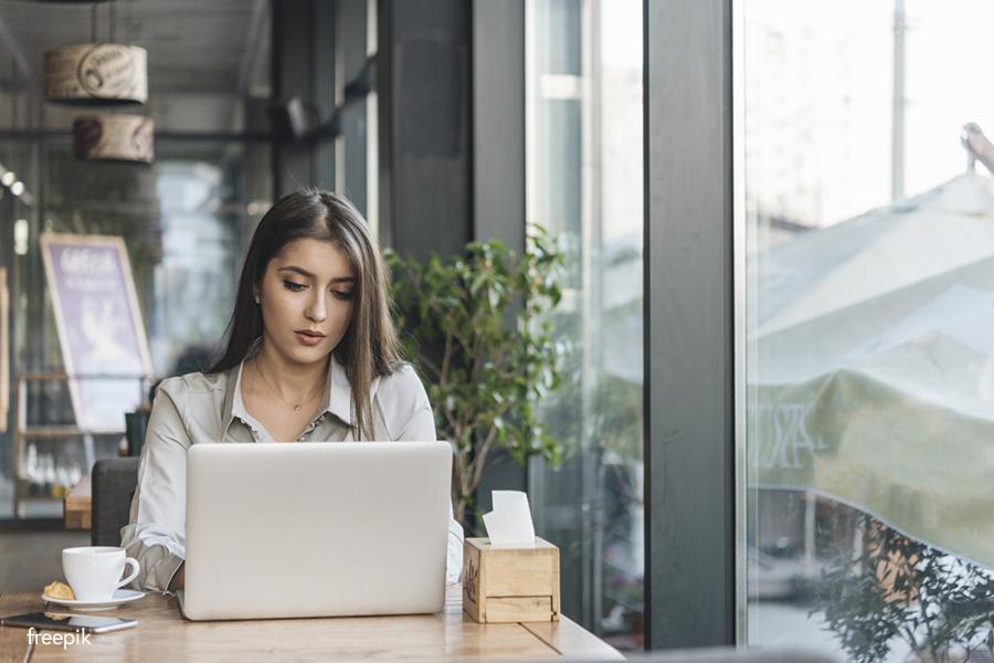 Woman typing on laptop in cafe - freepik