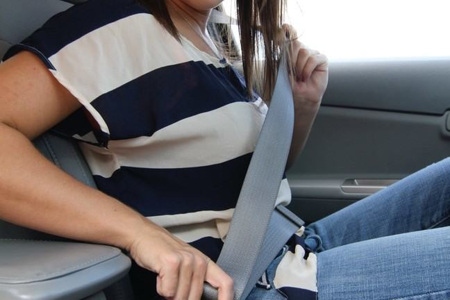 A woman fastens her seat belt.