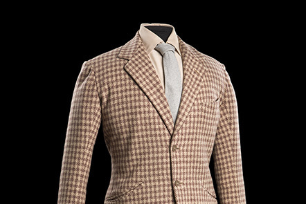 Tweed jacket with a white cotton shirt and grey tie underneath.