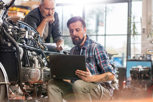 Two men looking at a laptop while working on a car engine.