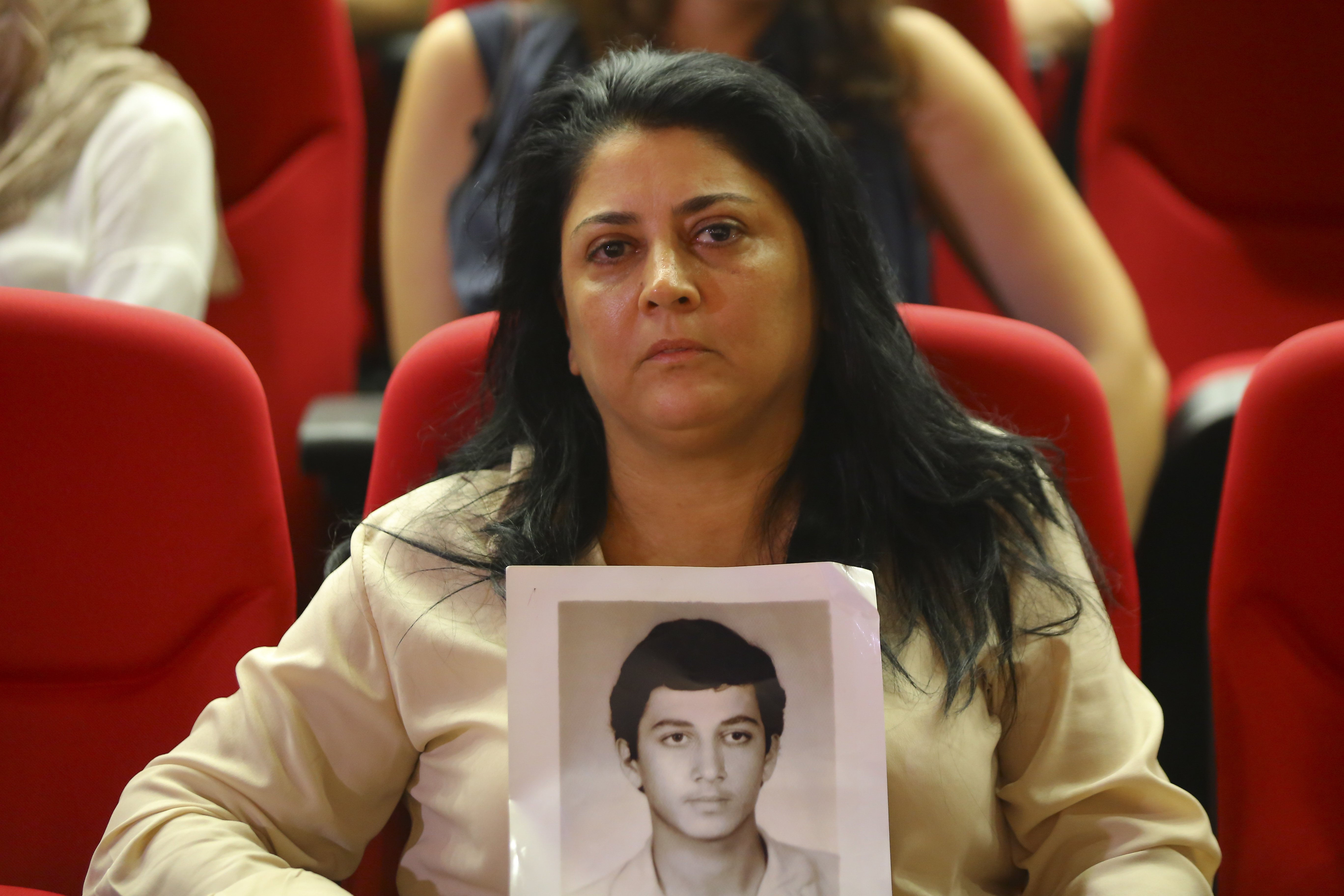 A woman holds up a photograph of her missing adult son.
