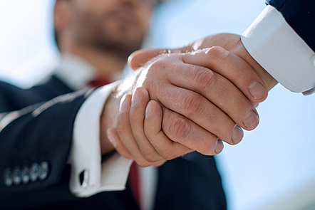 Men shaking hands as if concluding a business deal.