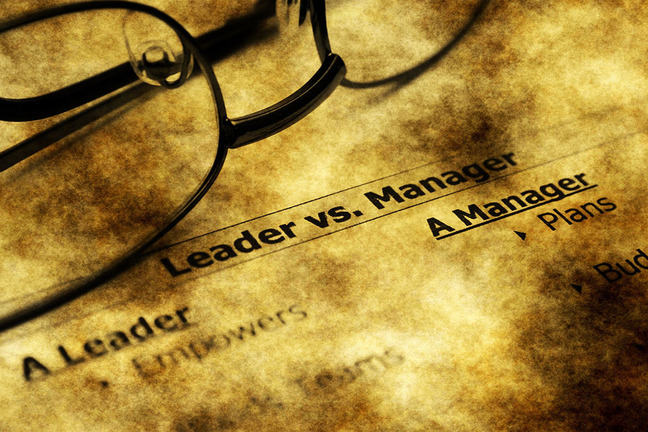Reading glasses on top of a paper and written on it the words Leader vs Manager
