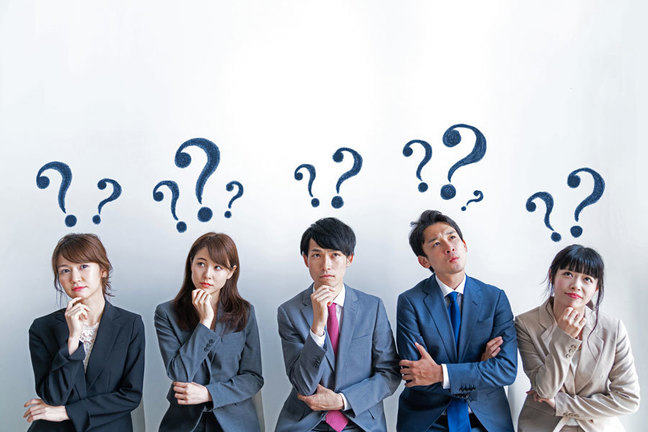 A group of 3 women and 2 men standing in a row, facing forward in a thoughtful pose with question marks hovering above their heads.