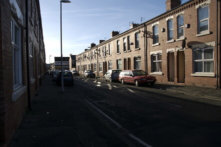 A picture of a residential row of terraces houses in Moss Side, Manchester.
