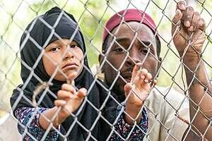 Man and young girl looking through wire fence