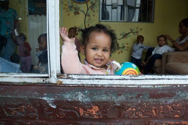 A girl leans out of the window in her daycare centre and waves to the camera.