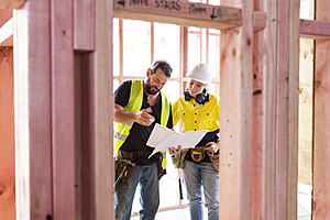 Male and female construction workers discuss a building plan