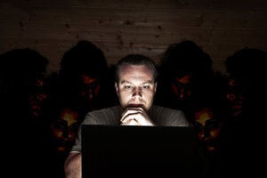 A cyber security threat – a man looks at his laptop, while people snoop over his shoulder