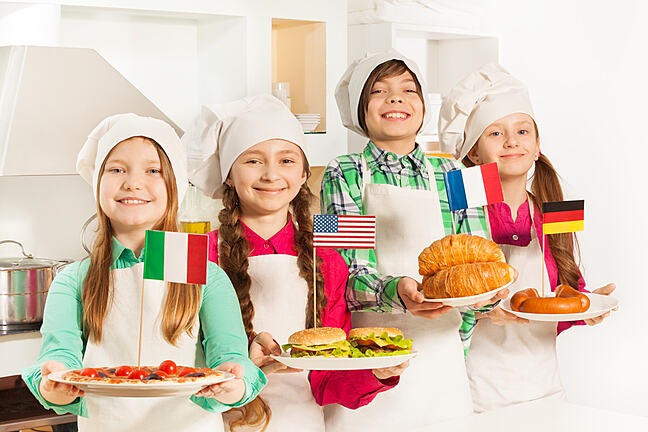 Children in chef hats holding food with country flags