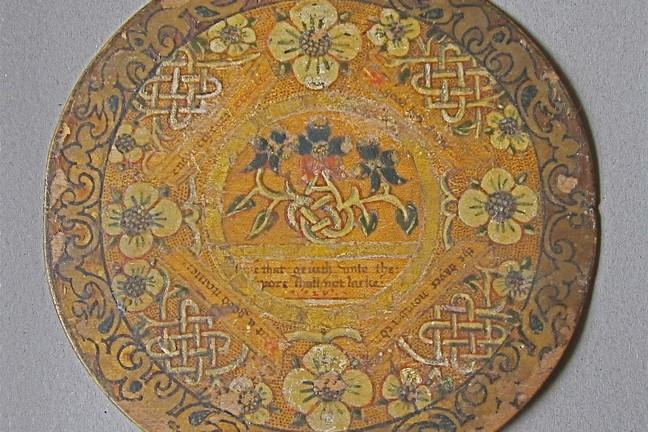A trencher circa 1600 made from wood. It is painted and gilded with designs of patterns and plant life.