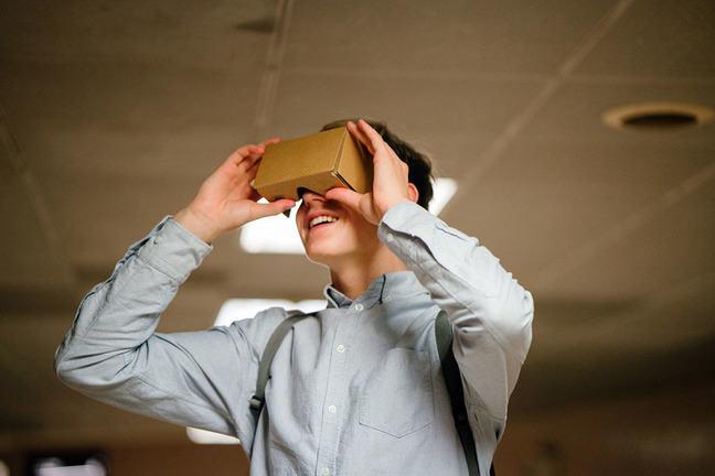 Man in grey dress shirt using brown cardboard VR glasses