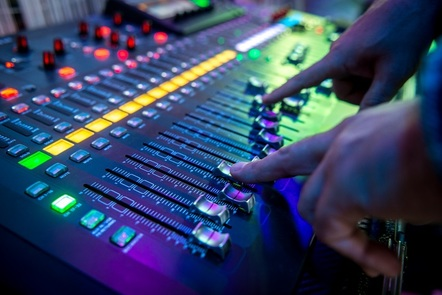 Photography of a person using a mix table in a recording studio.