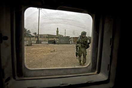 A US soldier runs for cover to report direct fire from suspected Iraqi insurgents as an American humanitarian and intelligence convoy enters an Iraqi village.