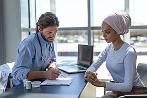 A healthcare professional consulting with a patient