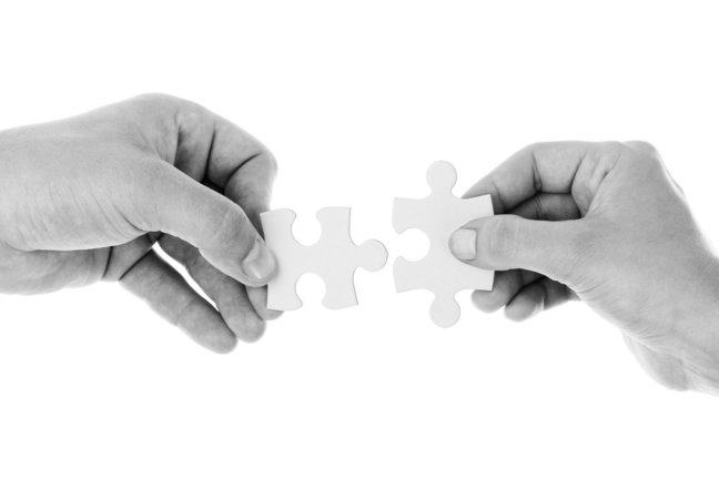 two hands connecting jigsaw pieces in black and white