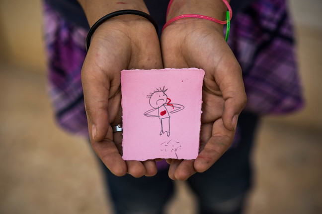 Two hands are together with their palms facing upwards. Resting on the palms is a piece of pink paper with a basic pencil drawing of a person with a red dot on its chest. You can tell the hands belong to a girl because she is wearing colored bracelets.
