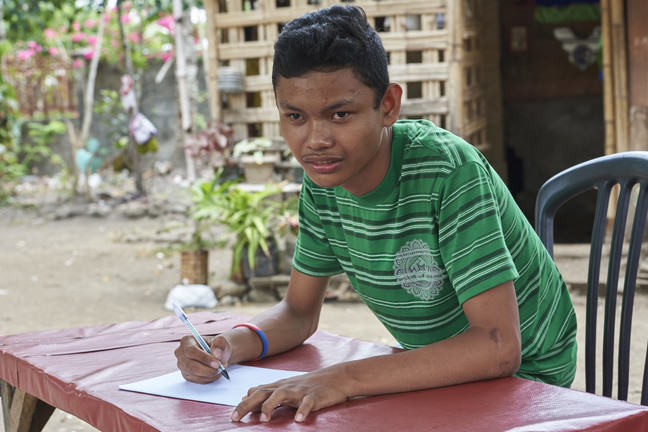 A teenager with cerebral palsy is writing at a table.