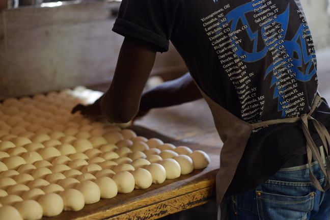 A worker in a bakery with their back to the camera, producing dough balls.