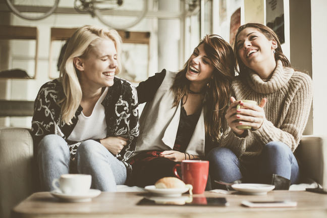 Three laughing and smiling girls sitting on a sofa with coffee