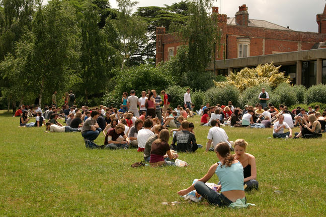 A photo showing many groups of students sitting on the grass socialising or working in front of a red brick building