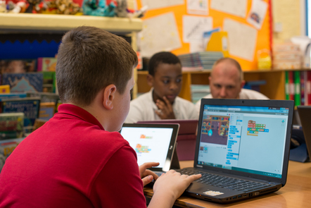 Child in a classroom progamming in Scratch on a laptop
