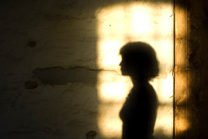 Shadow of a woman on a brightly lit section of wall