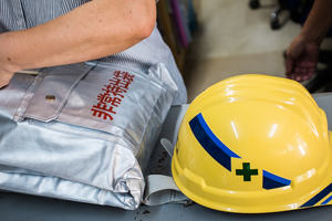 Man preparing a rucksack for an emergency with a safety hat.
